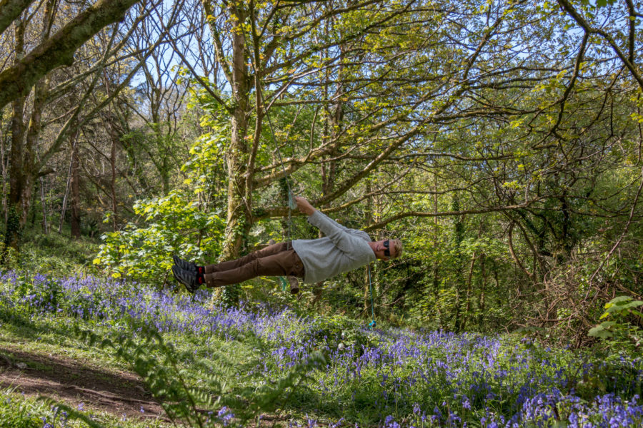 Dan almost laying horizontal as he swings on a rope swing amongst the trees in blue bell forest