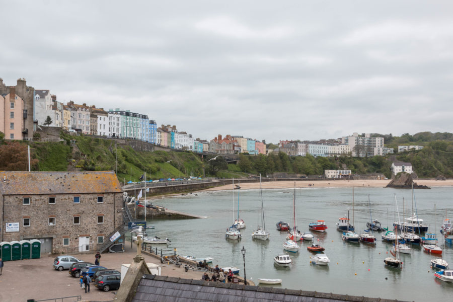Boats anchored in the bay at Tenby, colourful houses along the top of the hill.