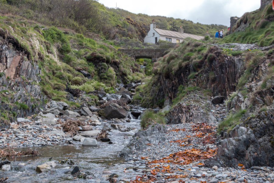 A small stream running through the rocks, a white building at the top.