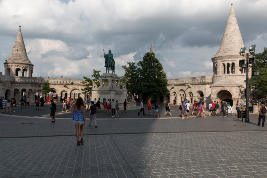 Tegan walking through a square towards are big statue