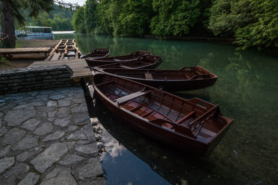 Wooden boats tied to a wooden jetty on the super clear lake water