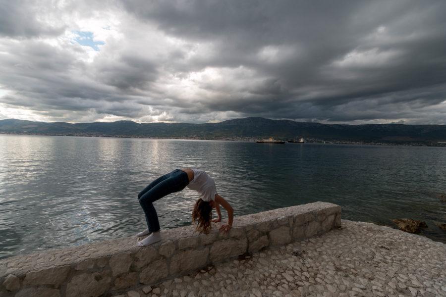 Tegan doing wheel pose, ocean behind, grey skies above