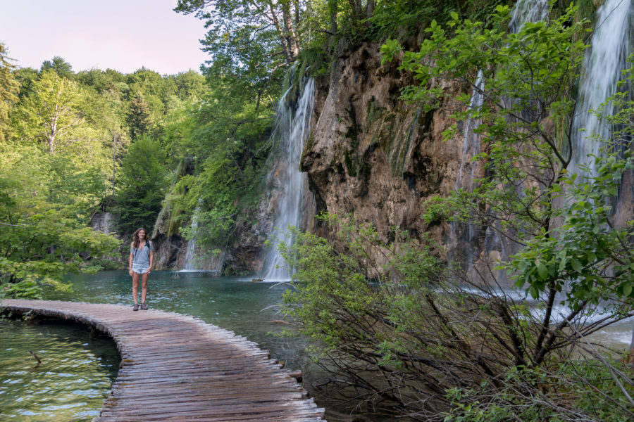 tegan standing on the wooden path through the lakes, waterfall to the right, green trees everywhere