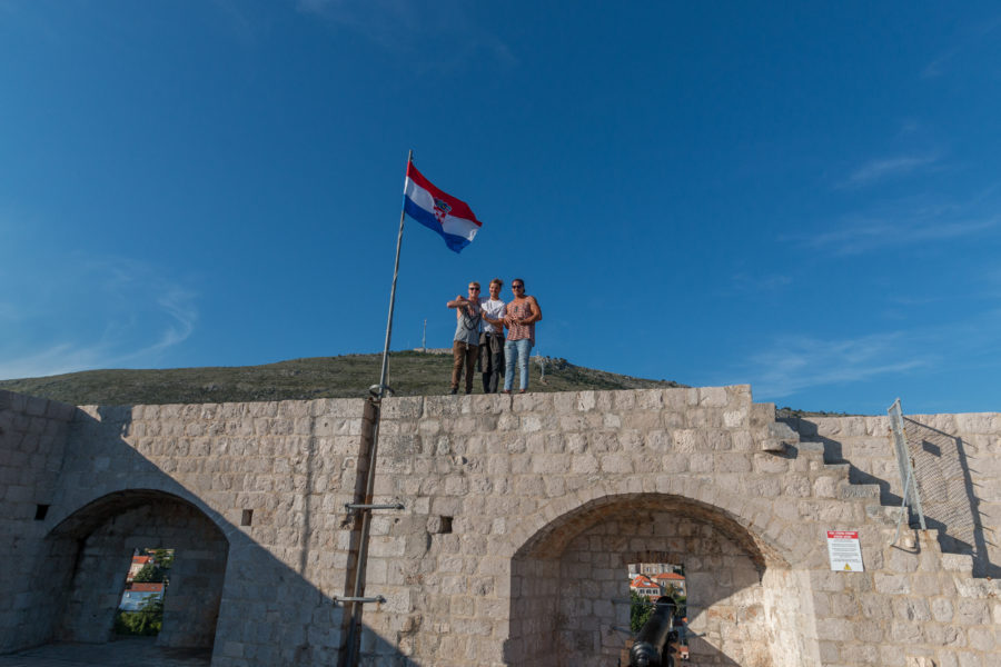 Boys standing on the wall under the flag
