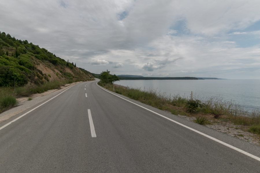 Road, sea to the right, hill to the left