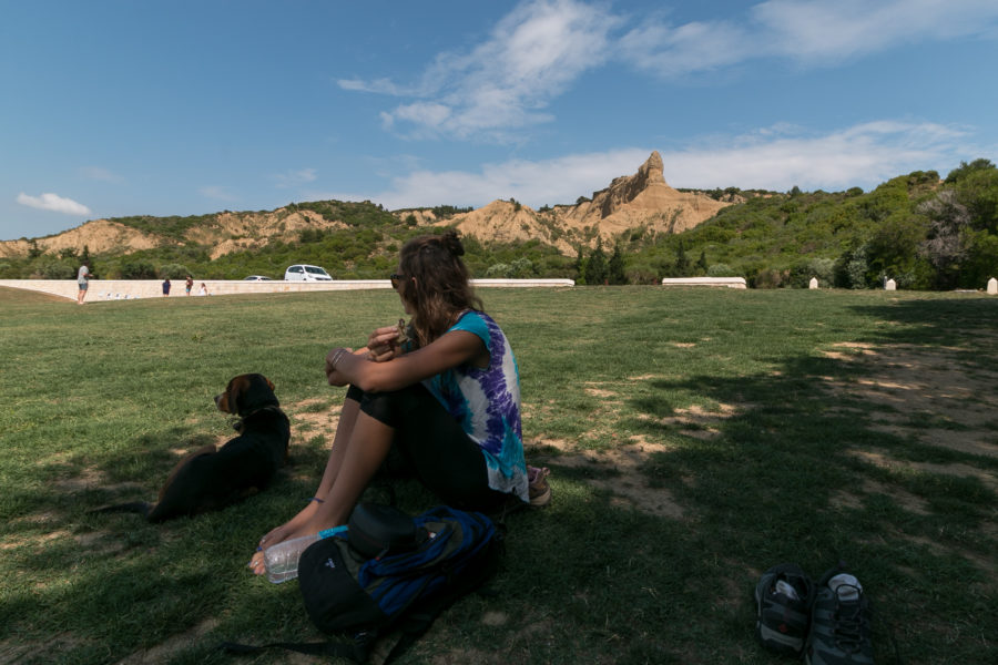 Tegz and a dog sitting on the grass, the rocky outcrop the soliders tried to ascend in the backgroun