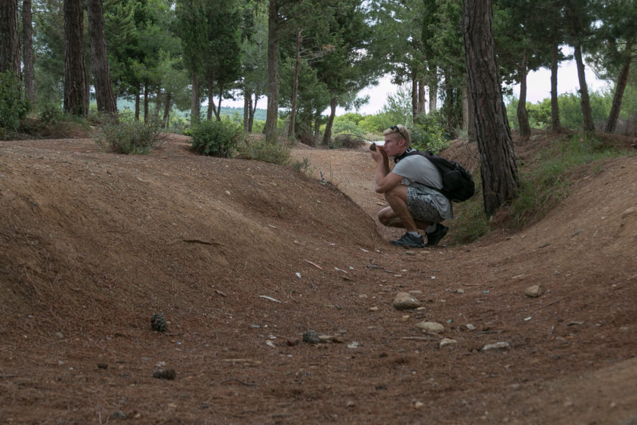 Dan crouched in a trench throwing a 'grenade'