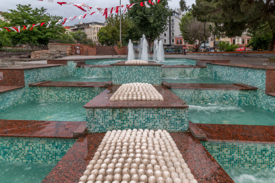 Water fountain with 3 levels, brown tiles on top blue tiles below the water