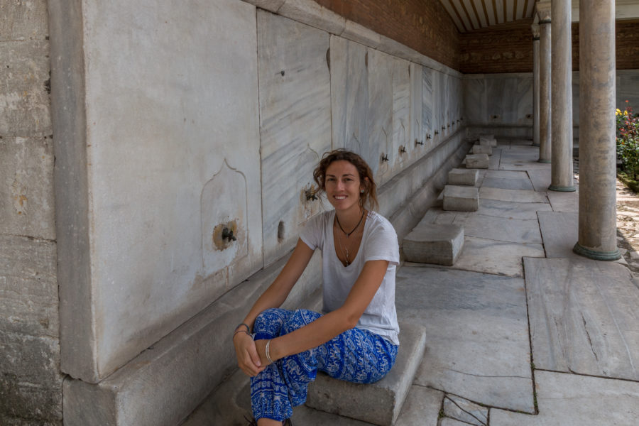 Tegan sitting on a concrete step, taps along the wall so you can wash your feet before entering the mosque