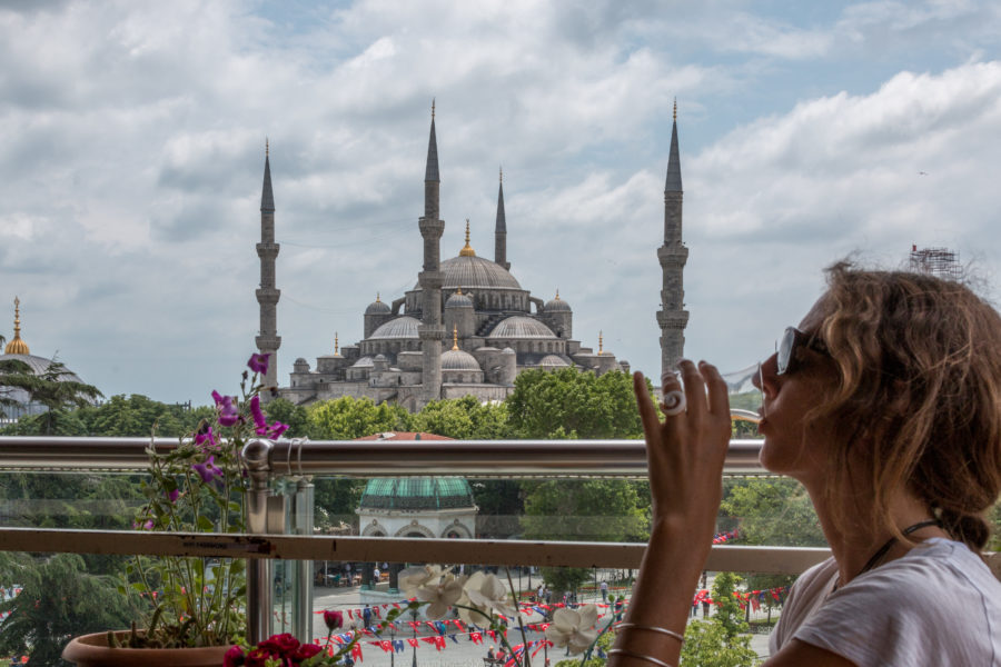 The blue mosque, Tegan drinking tea from the balcony of a cafe, cloudy skies behind, green park in front