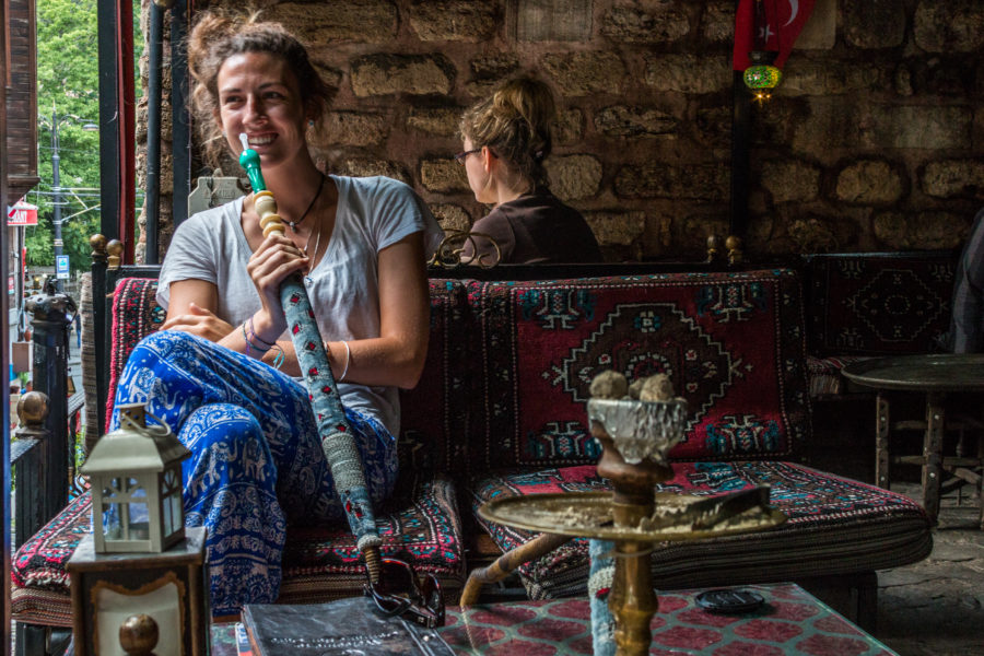 Tegan holding a shisha pipe on a cosy couch in a brick shack