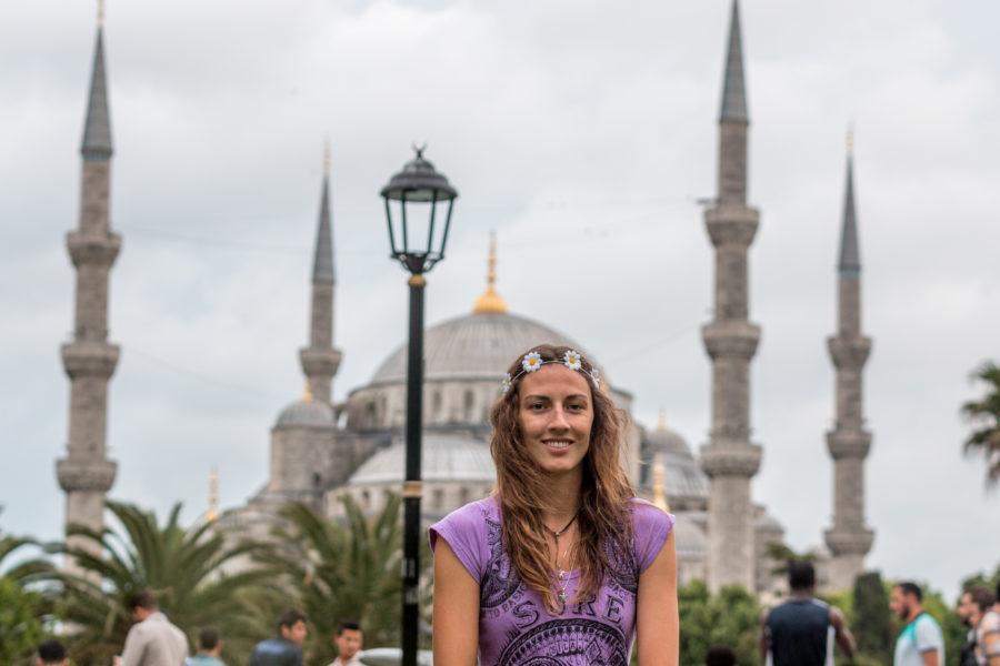 Tegan with flowers in her hair sitting in the park, Blue Mosque blurred in the background