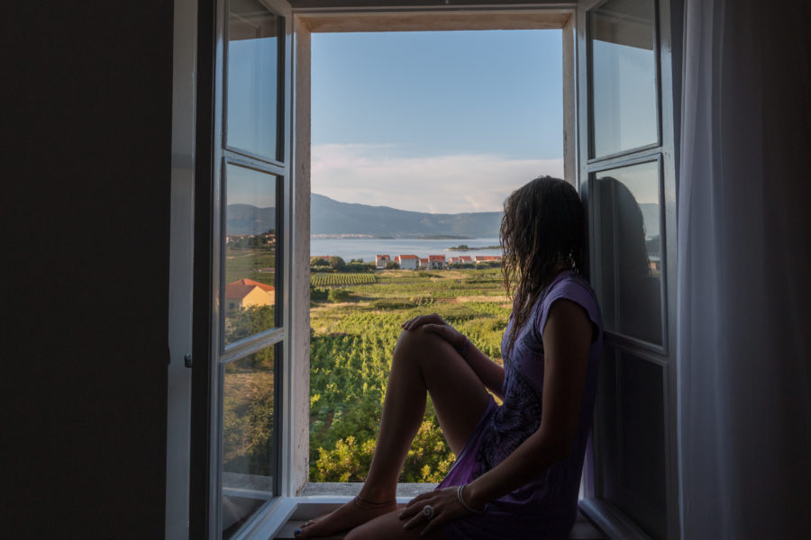 Tegan sitting in the window of the stone house we stayed in, looking out to the vineyard and sea beyond