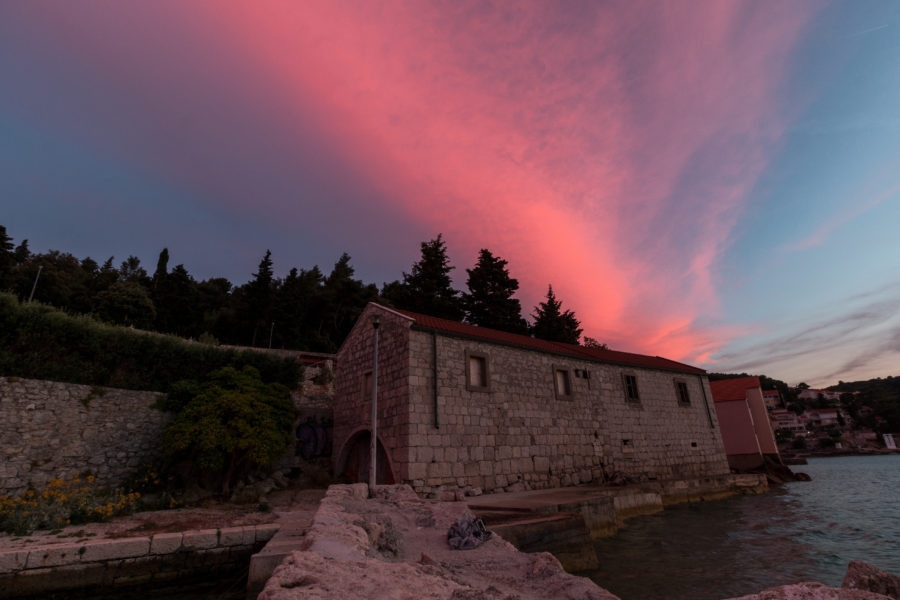 A fairy dust sunset, pinks, purples and blues over the sea and a stone house