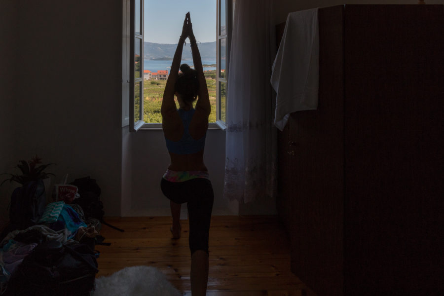 Tegan doing yoga with a view out the windows of the vinyard and the sea