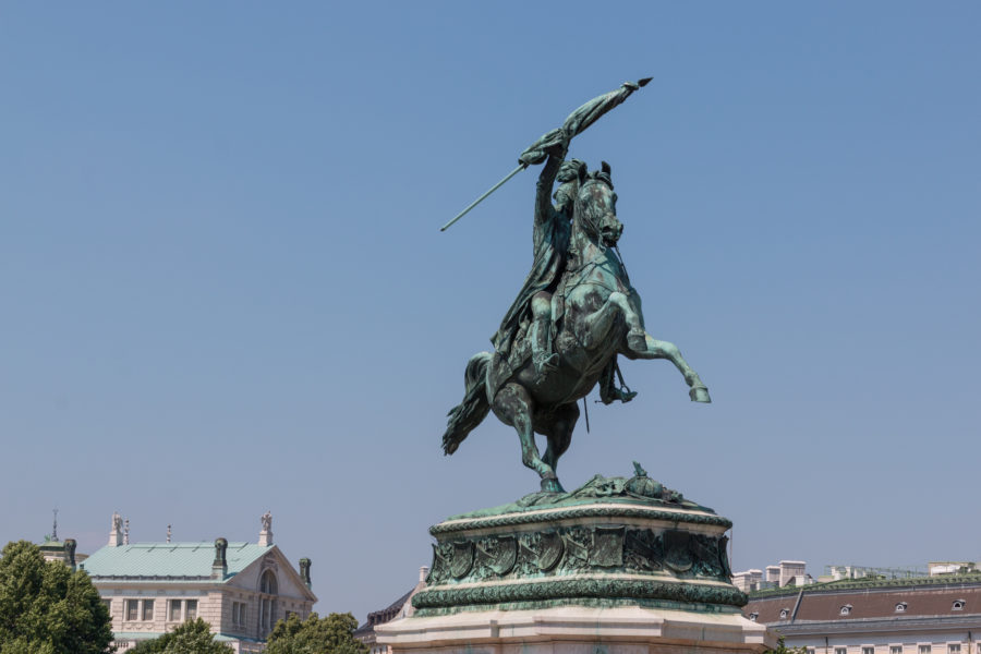 Statue of a man holding a flag riding a horse
