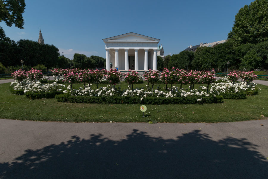 White building surrounded by lush green grass and white and pink flowers