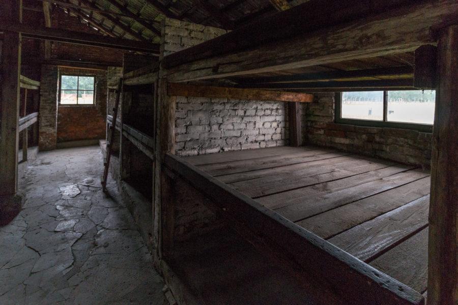 Inside a barrack, wooden bunk beds