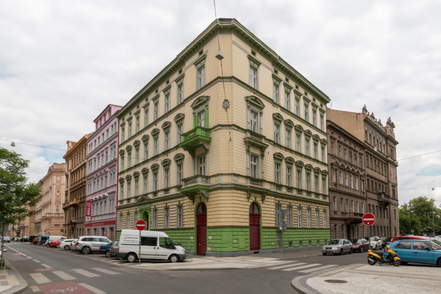 yellow and green corner building with red doors