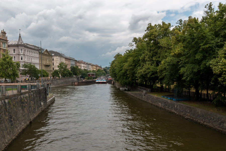 Vltava river, green bushes on the right, buildings to the left, grey skies above
