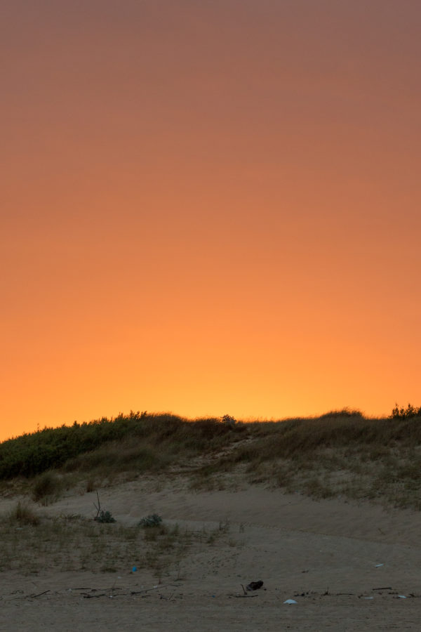 Glowing orange sky before the sun rises over the sand dunes at the beach