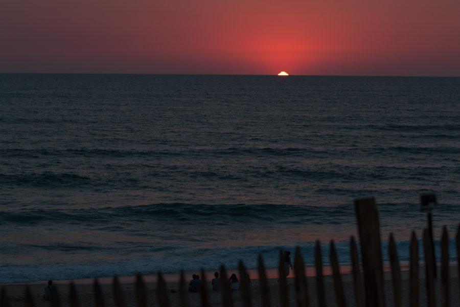 Last bit of sun shining over the blue ocean horizon