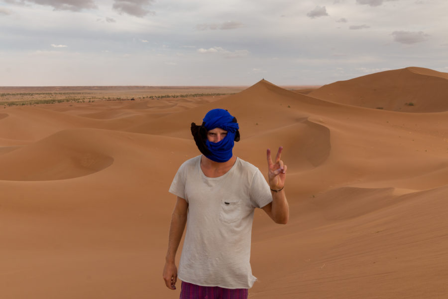 Daniel pulling peace fingers with nothing but sand dunes behind him