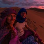 Sunset selfie on the dunes of the desert, pink and purple skies