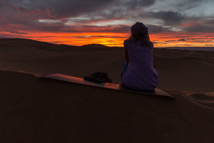 Tegan sitting on a sandboard with the sunset behind