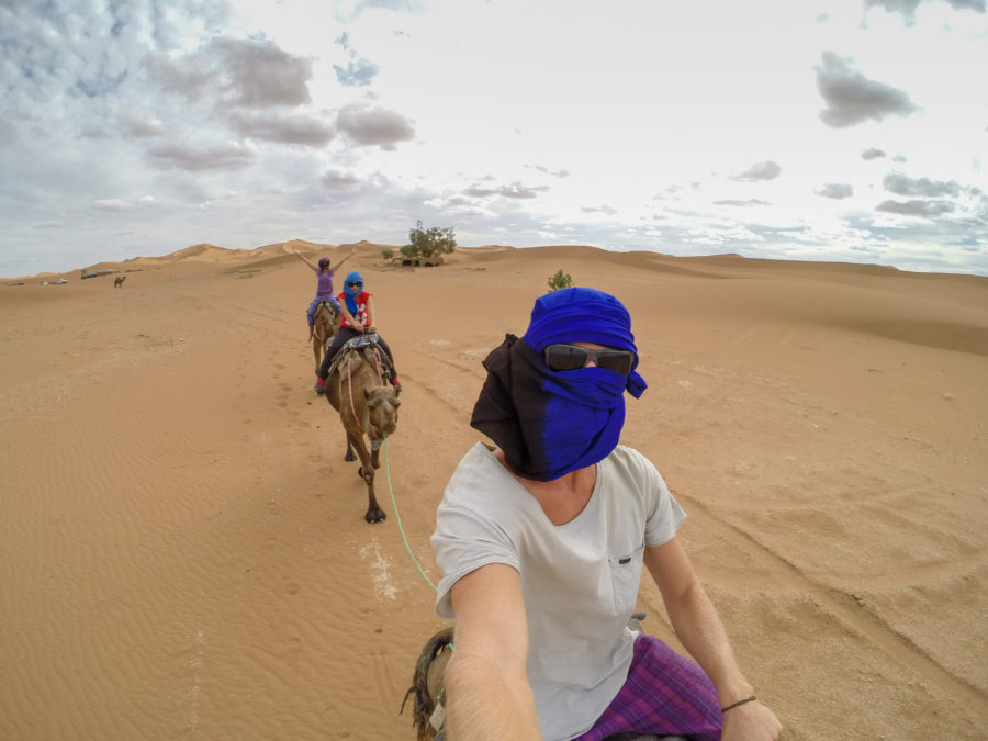 Dan taking a selfie during the camel walk, tegan a few camels behind