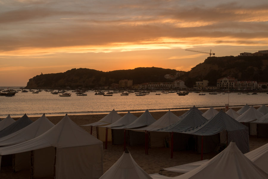 Sunset over the beach, beach huts on the sand, boats on the still lake
