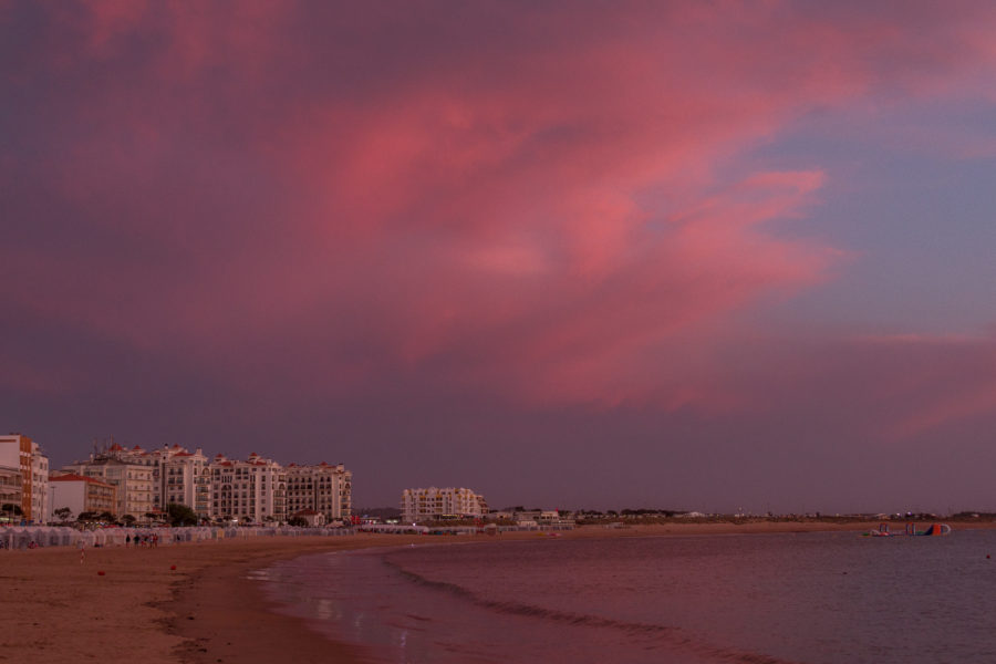 Pink fluffy clouds reflecting pink on the ocean, standing on the sand