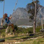 Tegan on a swing, table mountain range behind