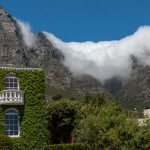 The table cloth over the mountain, house in the foreground covered in green creepers