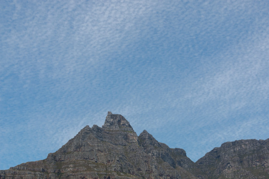 dotty clouds covering the blue skies, mountain range behind