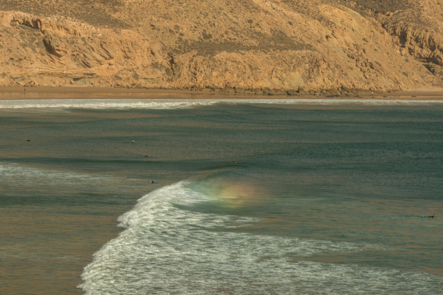 spray making a rainbow behind the wave