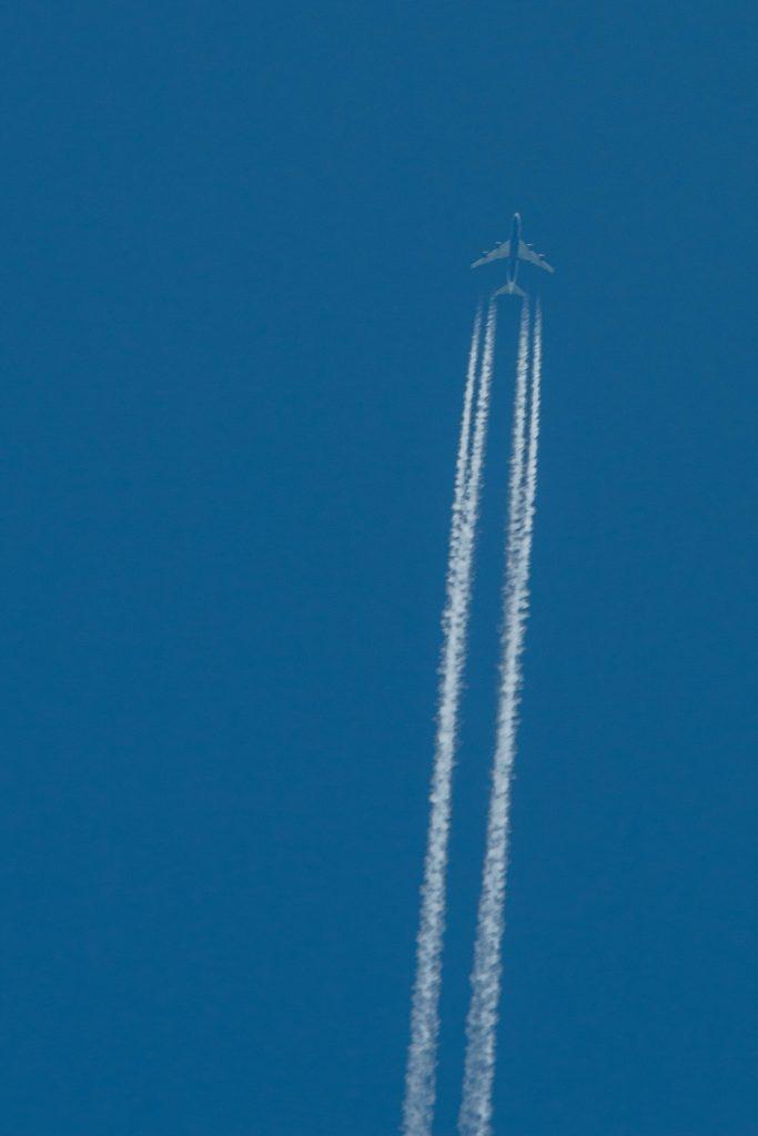 plane flying through the blue skies white jet stream behind it