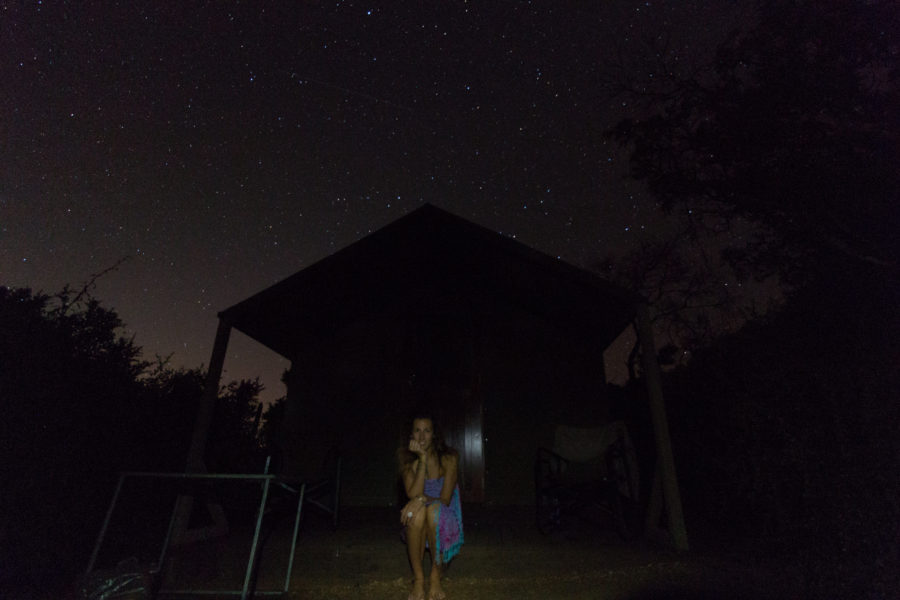 Tegan sitting on the deck of the cabin, starry sky above