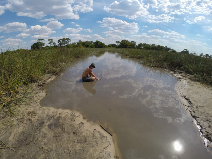Dan gathering water in the filthy brown swamp we swam in