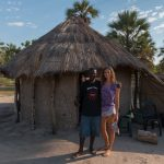 Tegan standing next to the local tour guide in front of his mud hut house