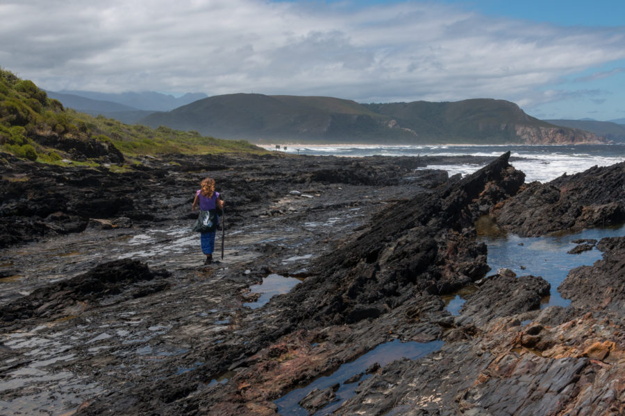 tegan walking along the black rocks with her gandalf stick
