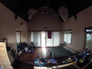 Inside our beach bungalow, all open plan living, wooden floors and mosquito nets over the bed