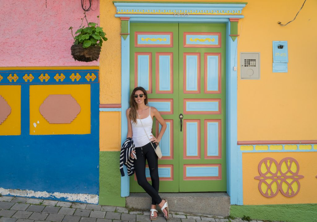 Tegan leaning against a very colourful door and walls